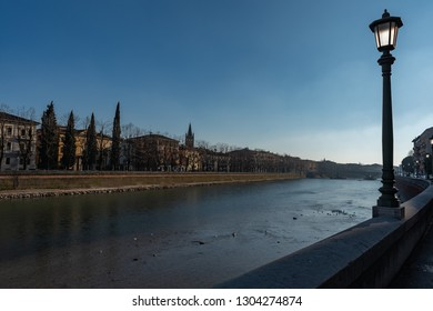 side view of the Adige river in Verona, on the right side an illuminated lamppost. horizontal image