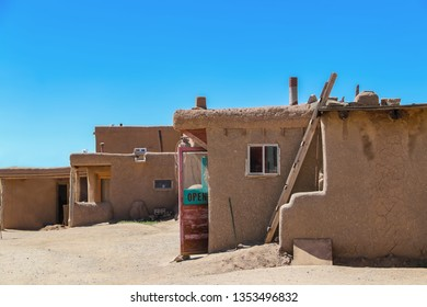 Side view of adobe mud buildings in a pueblo in the Southwestern USA, with shops with doors open for selling local crafts and foods to tourists