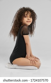 Side view of adorable cheerful girl in black sportswear and white knee socks posing while sitting of floor, isolated on gray studio background. Little professional female gymnast with curly hair.