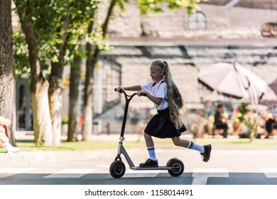 side view of adorable happy schoolchild with backpack riding scooter on street