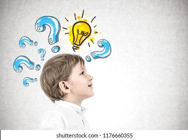 Side view of an adorable little caucasian boy with blond hair wearing white shirt and dark blue jeans and looking upwards. Yellow light bulb among question marks on concrete wall