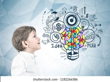 Side view of an adorable little caucasian boy with blond hair wearing white shirt and dark blue jeans and looking upwards. Colorful light bulb brain sketch, business idea concept