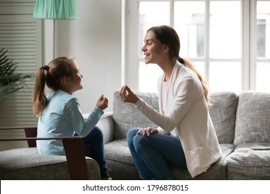 Side view adorable small preschool girl involved in speaking lesson with professional mixed race physiotherapist. Happy young mother teaching little daughter correct sounds pronunciation at home.