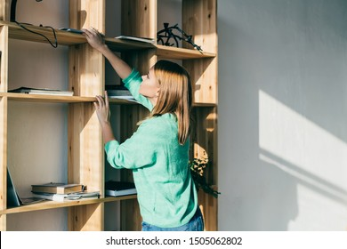Side view of adult beautiful female in casual wear taking magazine from upper shelf of shelve stand full of books and journals in bright living room