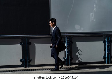 Side view of an adult businessman walking along the pedestrian way, A man took a hand pocket , A empty bilboard behind a businessman in blue suit, Asian businessman carry black bag on the shoulder.