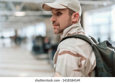 Side view of adult man wearing military uniform and situating in waiting room. Male model is looking for his wife indoors. Homecoming concept