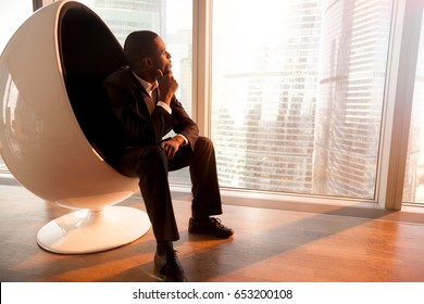 Side view of African american businessman holding hand on chin, sitting in design egg chair enjoying sunset, looking through big office window at city, deep in thoughts, dreaming of new opportunities