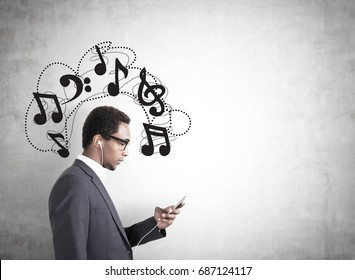 Side view of an African American businessman in a gray suit looking at his smartphone screen. He is wearing headphones. Concrete wall background with music notes on it. Mock up