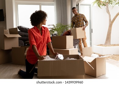 Side view of African american Couple unpacking cardboard boxes in living room at home