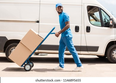 side view of african american delivery man with cart and boxes