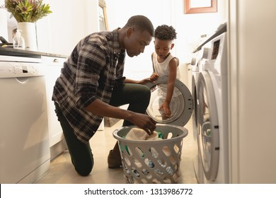 Side view of African American father and son washing clothes in washing machine at home. Social distancing and self isolation in quarantine lockdown for Coronavirus Covid19