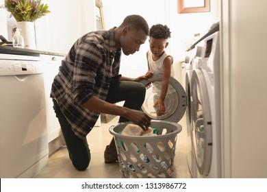 Seitenansicht des afroamerikanischen Vaters und Sohn, der zu Hause Wäsche in Waschmaschine wäscht