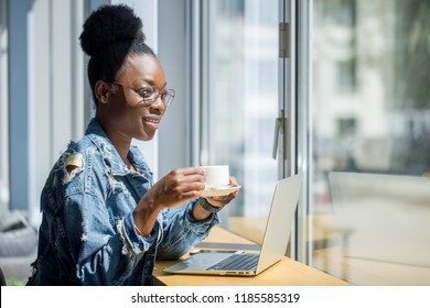 Side view of African american female student in jeans wear drinking coffee and studying online while sitting with laptop at the cafe , near the window with summer landscape