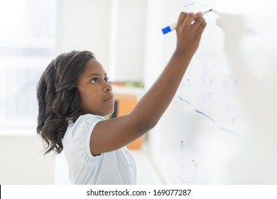 Side view of African American girl solving math problem on whiteboard in classroom