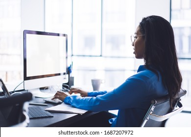 Side view of African American lady sitting in front of empty screen of monitor at black office desk in day time