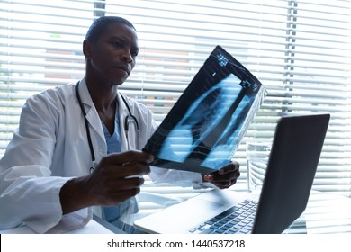 Side view of African American male doctor holding and examining x-ray report at desk in the hospital