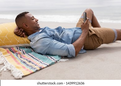 Side view of African american Man using mobile phone while relaxing at beach on a sunny day