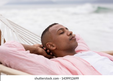 Side view of African american Man sleeping with hands behind head on a hammock at beach