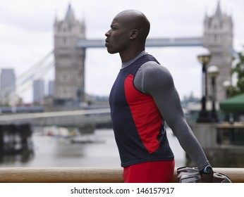 Side view of an African American man stretching in front of Tower Bridge in England