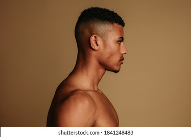 Side view of african american man standing on brown background. Portrait of shirtless muscular man with short hair.