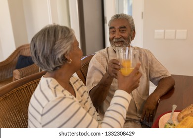 Side view of African American senior couple toasting glasses of orange juice while sitting at the dining table at home