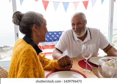 Side view of African American senior man holding hands of senior African American woman while having meal on a dining table at home