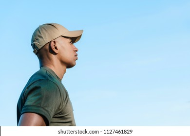 side view of african american soldier in cap against blue sky
