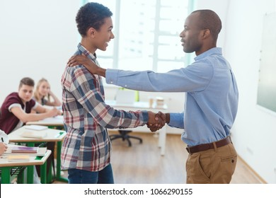 Side view of african american teacher shaking of high school teenage student in clasroom