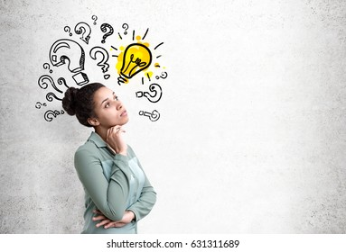 Side view of an African American woman wearing a green shirt standing near a concrete wall with a lot of question marks surrounding a yellow light bulb. Mock up