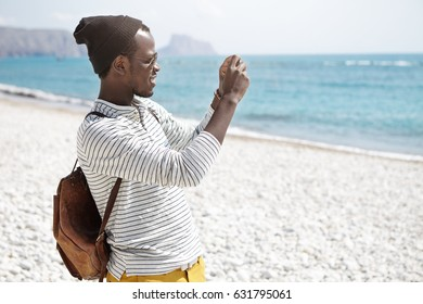 Side view of African American young man with backpack, in hat and striped shirt taking photos of seaside standing on beach alone, posting photo or video on popular social networks during his trip