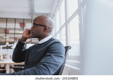Side view of african executive sitting at his desk using mobile phone. Young man at work answering a phone call.