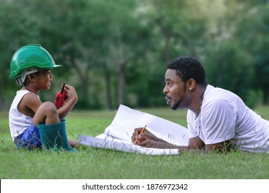 Side view of African father explained the construction with blue print to his son, lying on lawn at park, son in safety hat and walkie talkie or portable radio in hand