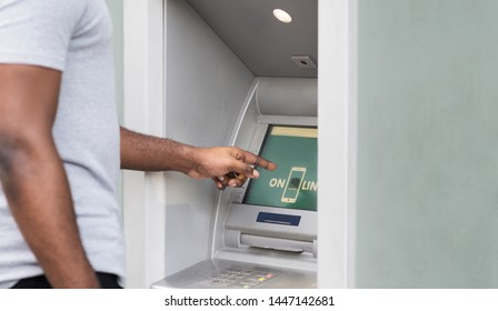 Side view of african man touching screen on ATM for enter his password, panorama, copy space