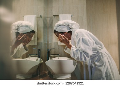 Side view of african woman in bathrobe washing her face in bathroom sink and looking into the mirror. Mature female cleaning her face in bathroom.