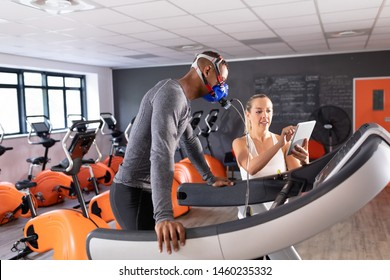 Side view of an African-American athletic man doing a fitness test using a mask while using a treadmill and a Caucasian woman showing his results inside a room at a sports center. Athlete testing