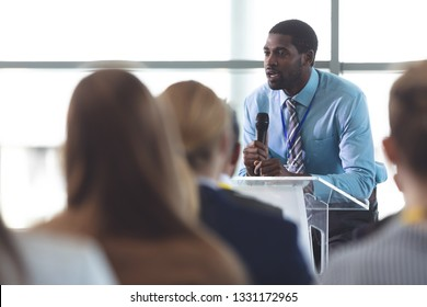 Side view of African-American businessman speaker speaking in a business seminar in modern office building
