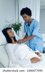 Side view of African-American female doctor examining female patient with stethoscope in the ward at hospital