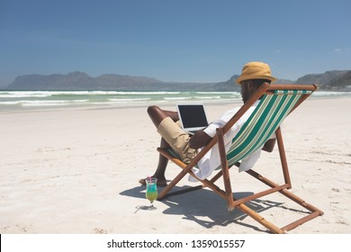 Side view of African-American man using laptop while sitting at sun lounger at beach on a sunny day. He wears hat
