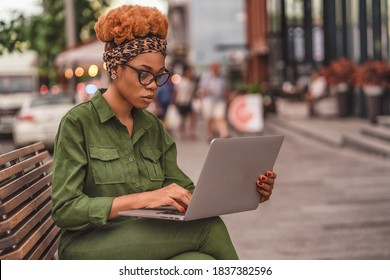 Side view of Afro American lady in glasses sitting on bench in the city and using laptop computer. Working lifestyle. Copy space