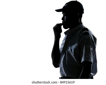 Side view of an afro American policeman blowing whistle in studio on white isolated background
