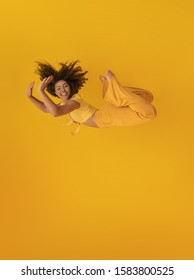 Side view of afro hair woman in zero gravity or a fall. Girl is flying, falling or floating in the air. Side view of person. Over yellow background. Getting sucked up. Woman being abducted.