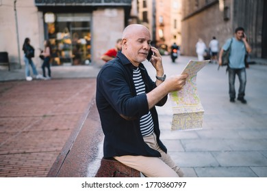 Side view of aged male talking on mobile phone while sitting on border in city center and searching location on map