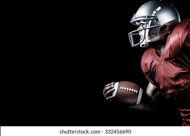 Side view of aggressive sportsman playing American football against black