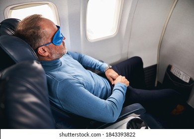 Side view of an airline passenger reclining in the seat in the first class cabin