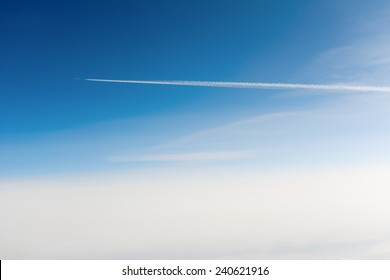 Side view of airplane contrail passing by against clear blue sky with sun flare