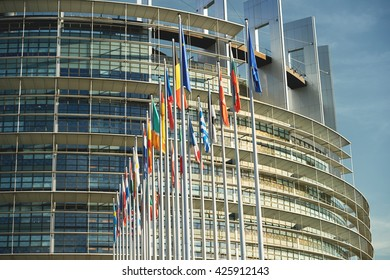 Side view of all members European Union flags waving in front of European Parliament building on a beautiful morning