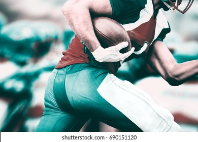 Side view of american football player who runs with the ball to make a touchdown. In the blurred background there can be seen his run protecting team.