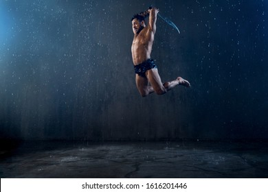Side view of angry tensed wet roman gladiator holding blade. Muscular agressive shirtless warrior in armor jumping in attack in rainy bad weather, dark atmosphere. Concept of ancient warrior.