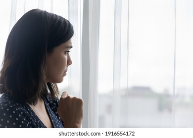 Side view of anxious sad young asian woman crying alone looking at window. Depressed millennial female going through hard bad life times cheating betrayal of beloved man divorce separation. Copy space