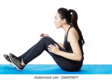 Side view of an Arabian woman doing crunches on the mat, isolated on white background